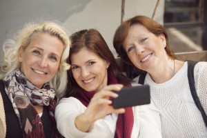 Happy group of mature women having fun with mobile phone