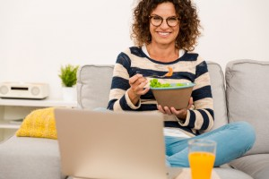 Beautiful woman at home making a pause of work to eat a salad